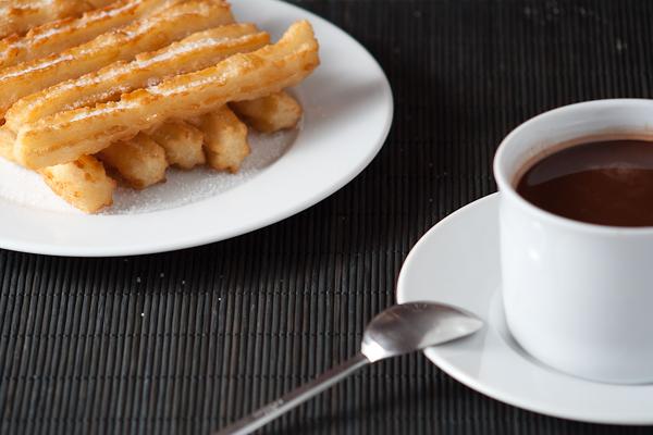 Churros caseros con una taza de chocolate caliente