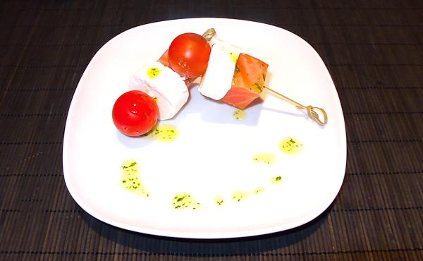 Pinchitos de salmón marinado con medallones de queso de cabra, tomate cherry y aceite de perejil