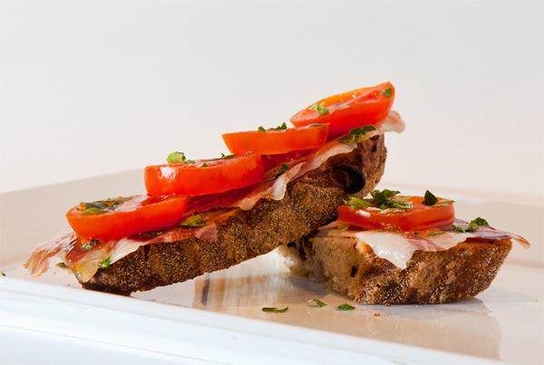 Jamón ibérico con tomate sobre una tostada de pan de aceitunas negras, tomates secos y orégano aportada por el blog Mil y una especias